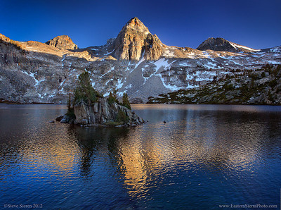 Rae Lakes and Painted Lady in Kings Canyon National Park, Sierra Nevada Mountains  Went on a little adventure to capture this image, so if you're not into adventure read no further. I won't be talking about the technically boring parts of photography either. I had a friend mention he was heading out the highly popular Rae Lakes on the Pacific Crest / John Muir Trail. I've always wanted visit the area just to see the terrain and take a few photographs. I ended up in a small group of 5 backpackers spending the first night at Charlotte Lake past Kearsarge Pass. I enjoyed the changing light in the late afternoon and early morning.  The only reason I came out to this trip was to make it to Rae Lakes so when a couple of friends mentioned they would be staying at Charlotte Lake I was a little bummed but made a decision to leave the group and go to Rae Lakes. I knew of a little pass between Dragon Peak and Gould Peak, a class 2 and maybe class 3 travel. For me this was the adventurous way out of the area with lots of cross country travel and route finding. Seeing more of the mountains just adds fuel to my soul and it was a shorter trek to getting to the Onion Valley Trail Head where our cars were. After making it over Glen pass (12k) on the second day and photographing Rae Lakes we set Dragon Pass. The hike started on lightly used trail that faded quickly once we hit Dragon Lake. We took a ridge route up to the higher unnamed lakes just below the pass. Mostly all talus hopping and crossing some snow but there was a pretty steep snowfield with lots of lose scree on top of it to make it to the top of the pass. We didn't see a single person that day.  We made it to about the last 100 ft below the pass when someone in the group mentioned this was beyond their comfort level and wanted to turn around unless I could find an easier route that was much safer with out the far drops below. I took my pack off and left the poles and climbed out of view only to make it into a higher gully with a steeper scree slope only yards from the top of the pass. The pass where it was only 5 miles all down hill to the car on the other side. The other option was to climb over Mt Gould to make it to Kearsarge Pass but again this beyond some comfort level so I okay we'll turnaround knowing it was a 17-18 mile trip back to the car over 2 passes. We made it back down to Rae Lakes by 5pm but I kicked a tree root and agitated my knee. I wanted to make it over Glen Pass since I was down to my last bits of snacks and food since I had planned on getting out Sunday. The other guy I was with said he had extra meals and breakfast so we stayed at Rae Lakes for the night. Turns out he had no breakfast so I emptied less then ounce of oatmeal and a few dried banana slices into a pot of hot cocoa before we hiked the 12 miles overs over 2 passes the morning. The things we do to see something new and to keep others safe... .  Hiking long distances doesn't make a photo better then it is but there are some that enjoy a good adventure here and there!