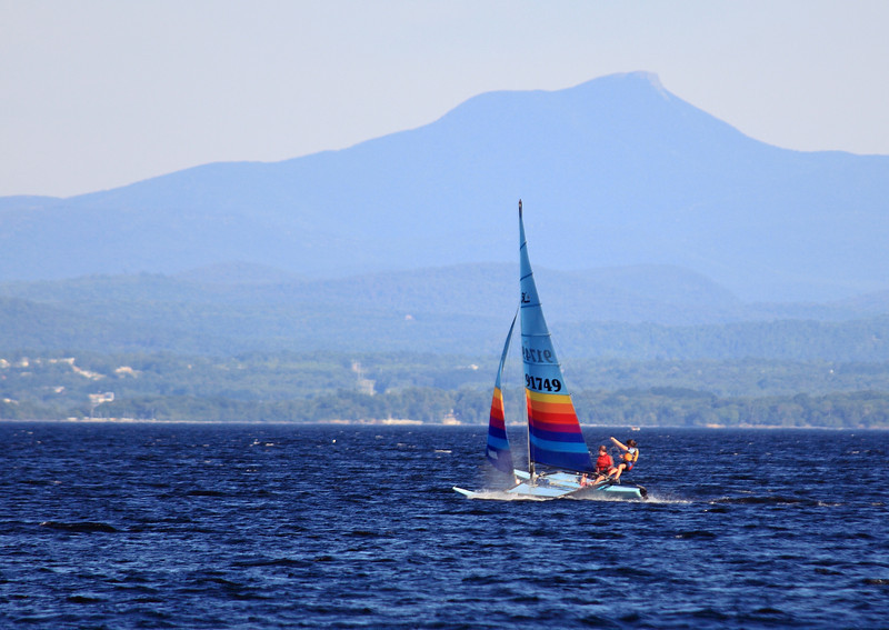 Neighbors sailing their Hobbie Cat on Lake Champlain with Camel's Hump, Vermont, in the background.