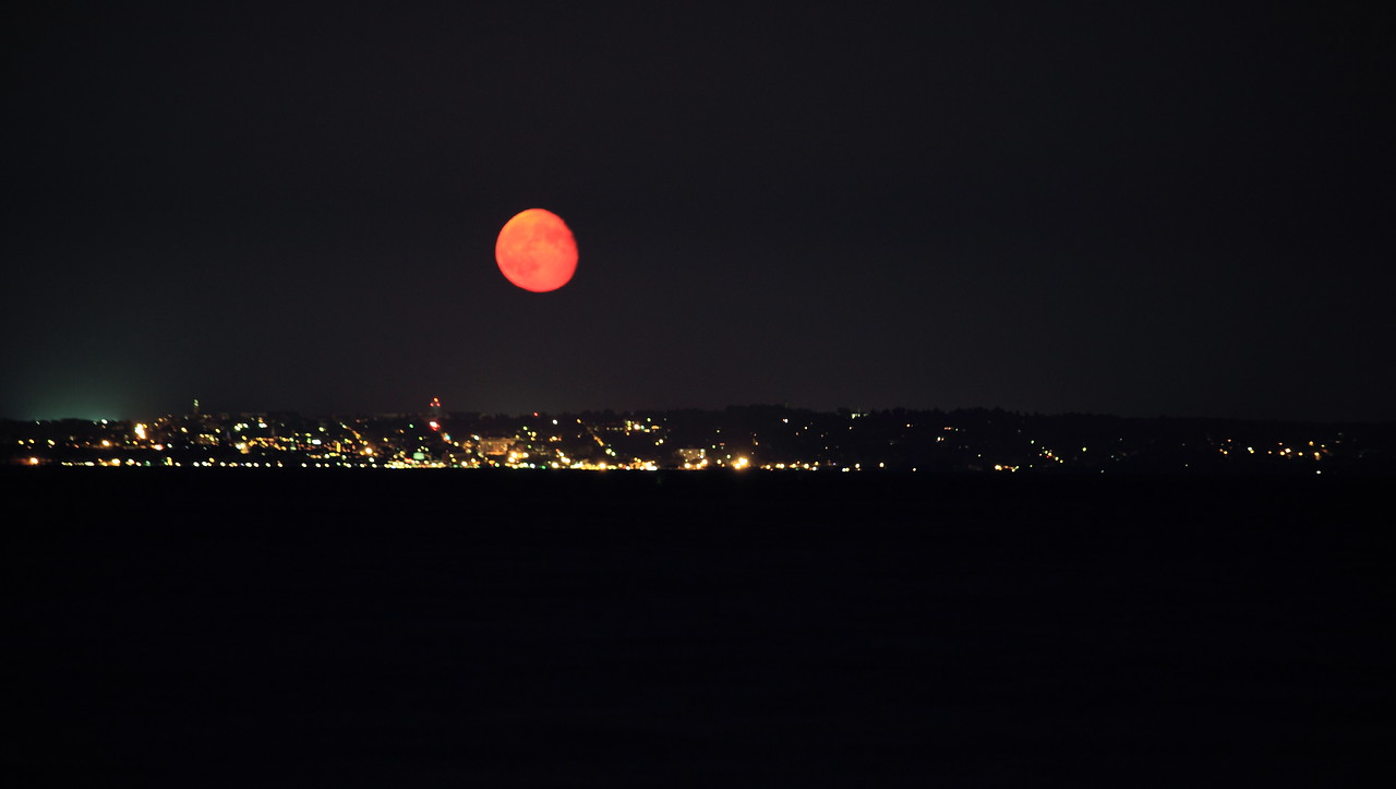 The moon rising red over Burlington, VT.