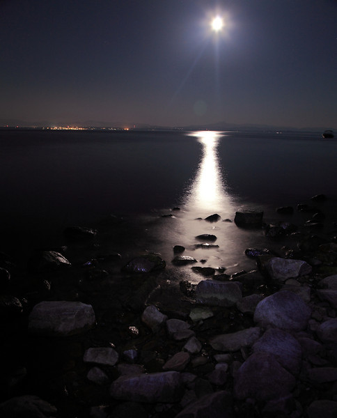 Full moon pouring light on the shore.  NY side of Lake Champlain with Burlington, Vermont, in the background.