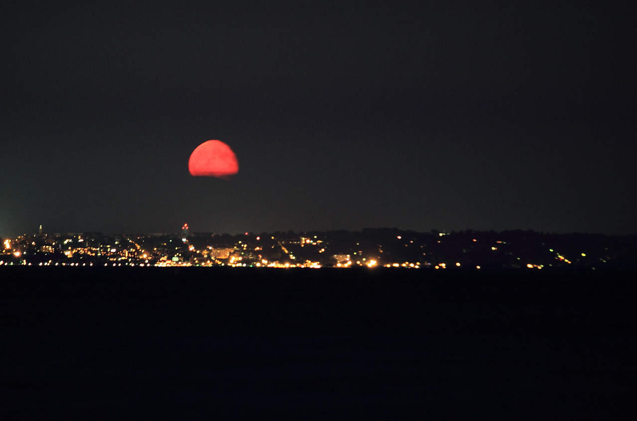 The moon rising red over Burlington, VT, and Lake Champlain. The Green Mountains in the background, not visible this night, are blocking the lower portion of the moon from view.  Minimal image processing here; this is just what it looks like.