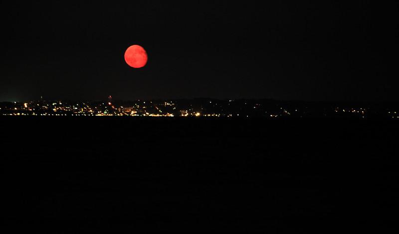 The moon rising red over Burlington, VT.