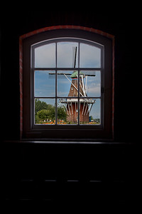 a Dutch windmill used for grinding grain into flour juxtaposed through its upper floor window