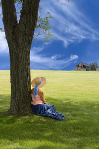 a woman sitting under a tree and looking at a barn