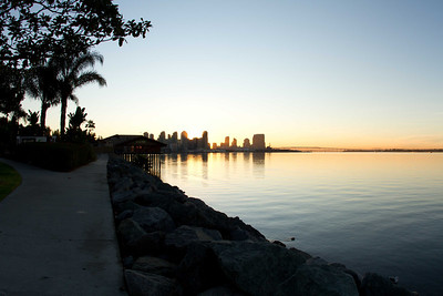 20120113-IMG_0866 Winter sun rises behind downtown San Diego as seen from Harbor Island walkway.  Coronado Bridge can be seen to the right of downtown.