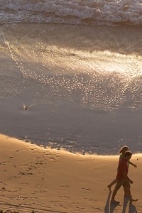 Footprints in the sand disappearing with the incoming tide and sunset