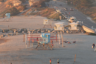 "Winter is the ""off season"" for beach going in Southern California, but the warmest winter in recorded history has kept the beaches busy.  Extra lifeguard towers are moved back from the beach for storage during the winter when our biggest swells and beach sand erosion are most likely to occur.  ""The shop"" sits at the south end of the far bluff, on the edge of the South Carlsbad State Beach campgrounds.  The shop is the base station for the State Beach lifeguards. It was my base when I was a student working as a lifeguard to help pay for my college education, more than a couple of decades ago."