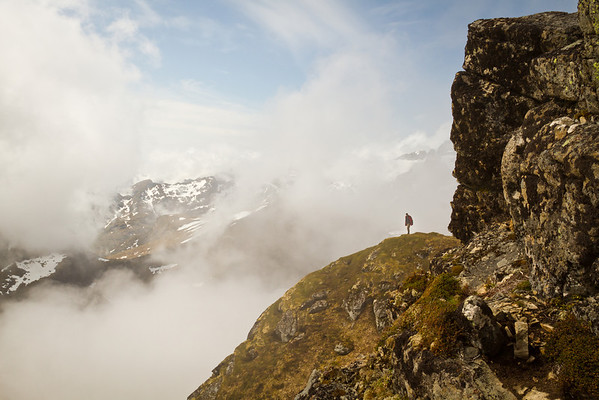 The clouds begin to clear as Michal reaches the other side of a steep rocky ridge, unveiling the massif of Monkebu.
