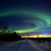 """I caught a whiff of the aurora on the IRF""""s All-Sky Camera. I grabbed my gear and headed out towards the back of the mines. On my way to the top, I caught a glimpse of a beautiful aurora forming over the city against the city lights of Kiruna, Sweden."""