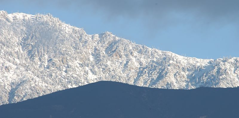 First snow after fires in Rancho Cucamonga. Black hills in front of snow covered mountains.