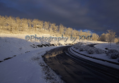 a snow covered road in the morning light