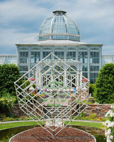 A sculpture by artist Hans Godo Frabel in front of the conservatory at Lewis Ginter Botanical Garden.