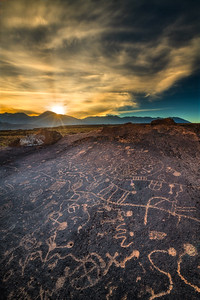 "The Sky Rock Petroglyphs located near Bishop, CA are a special and scared place indeed. Sky Rock is kept secret from the general public due to its special patterns and its rarity. Those people in ""the know"" don't share its location so that fewer people will visit and its condition could be kept as pristine as natural forces allow.  After a fair bit of searching online, I was able to narrow down the possibilities.  So, off I headed for a hike not sure how things would pan out. To my pleasant surprise I was able to locate the petroglyph without too much trouble (Phew!).    It was fascinating to see the enormous petroglyph firsthand and consider the artist who, probably many hundreds of years ago, composed the intricate petroglyph forms. I have to admit that standing alone above Sky Rock taking in the extraordinary distant views of the High Sierra and the overall magnitude of the high plateau was very inspirational. A beautiful sunset made the evening even more special!"