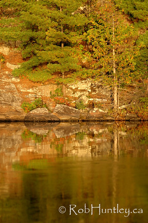Trees and boulder reflected in Lac a la Truite, near Wakefield, Quebec.