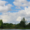 A beautiful cloudy blue sky viewed from a river in front of an island