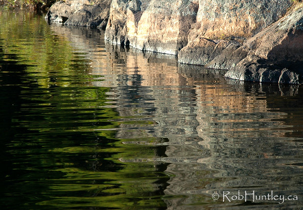 Granite Reflection. - Rocky outcrop reflecting in the lake's surface.