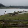 Boats on shore of the foggy lake.