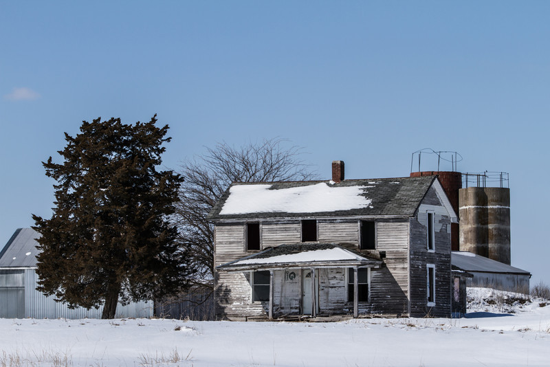 An old farmhouse next to the highway in the winter.