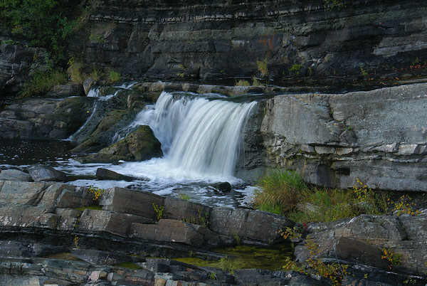 A small portion of the Hog's Back Falls. In the autumn the Falls flow powerfully down the Rideau River, as the river is lowered in preparation for the coming winter. During this time of year, small subsidiary waterfalls form as excess water flows over the rocky outcroppings surrounding the main Hog's Back Falls.  Photo taken 28 September 2010.
