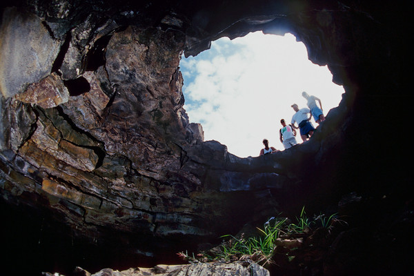 visitors investigate opening of a lava cavern, Kona, Hawaii