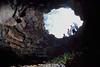 visitors investigate opening of a lava cavern, Kona, Hawaii