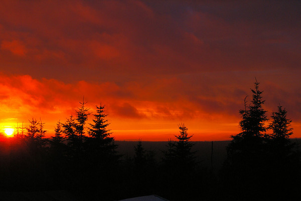 As the sun dips below the horizon, the sky ignites into deep reds and oranges.
