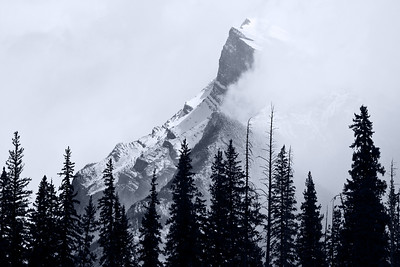 Fresh snow and swirling clouds on Mt. Rundle, one of the most famous mountain peaks in Canada.