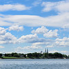 A view of a big church from the river under a beautiful cloudy blue sky