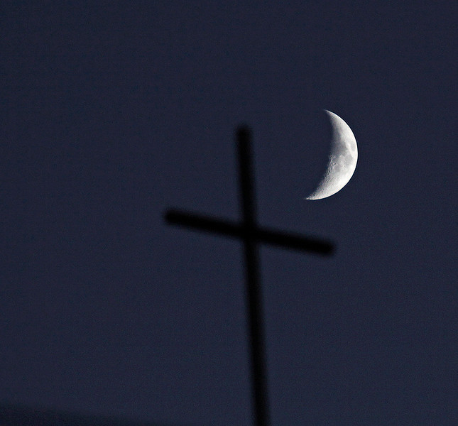 PRINTS NOT AVAILABLE  <br /> A waxing crescent moon near a church in Mackey Monday, Sept 29.