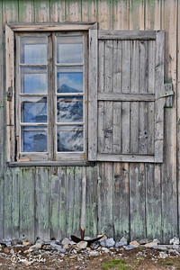 Reflection of the mountain in the old mining hut at Blomstrand Is, Spitsbergen