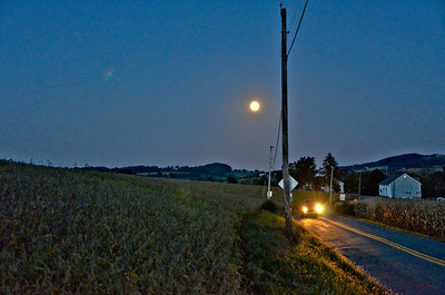 "On the way home I spotted the moon rising and pulled over as soon as I could.  Just goes to show that part of getting a picture is finding a place to pull over and park.  All these pictures suffer from hand holding the camera.  A tripod would have helped immensely. There was, in all the pictures, substantial post processing.  Smoothing artifacts, and adjusting brightness, contrast and exposure in Lightroom.  In Corel Photopaint I lightened the corn a little to bring out the detail which also improved the ""Moon Glow"" of the picture."