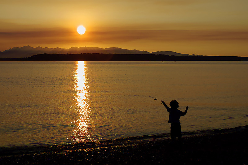 Boy enjoying the Edmonds beach, throwing a rock to the downing sun. The color in the sky was due to smoke from a large fire.