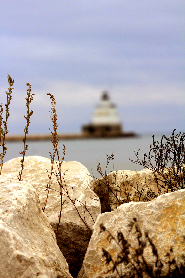 The first lighthouse to mark the harbor at Manitowoc was constructed in 1839, making it one of the older lights on Lake Michigan. The present structure was built in 1918, and sits at the end of a long breakwater that protects the harbor. An elevated catwalk once allowed the keepers who dwelt on shore to tend the light in inclement weather. The tower originally housed a fifth-order Fresnel lens, which was removed in 2002 and placed on exhibit in the nearby Wisconsin Maritime Museum. A more modern tower marks the end of the south breakwater.<br /> <br /> In 2009, the Manitowoc Breakwater Lighthouse, deemed excess by the Coast Guard, was offered at no cost to eligible entities, including federal, state, and local agencies, non-profit corporations, and educational organizations under the provisions of the National Historic Lighthouse Preservation Act of 2000.