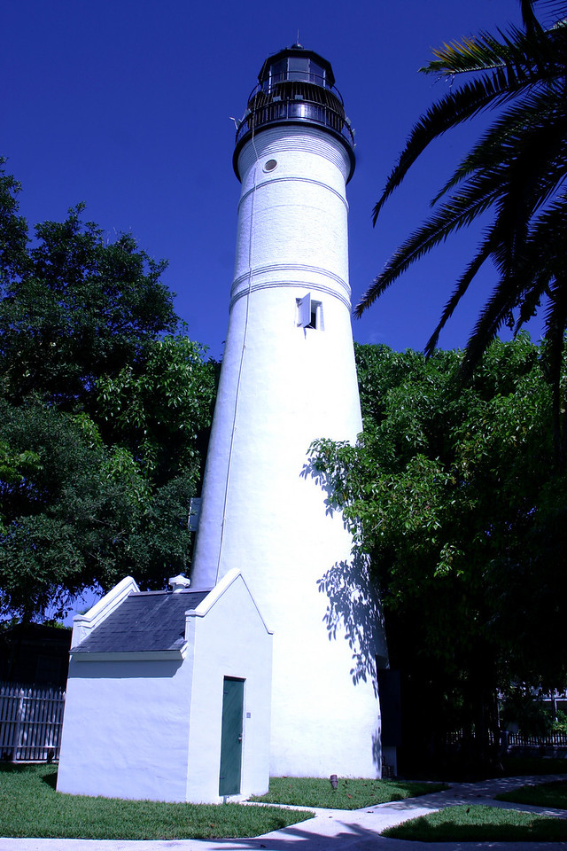 The Key West Lighthouse and Keeper's Quarters Museum:<br /> A beacon at the Corner of America<br /> <br /> Built in 1847 to aid to ships navigating dangerous reefs off the lower Keys, the Key West Lighthouse now stands sentinel over one of Florida's finest historical sites. <br /> <br /> The tower was originally 46 feet high and powered by 15 oil lamps with 15-inch reflectors, but was extended to 86 feet in 1894. Inside visitors now climb 88 iron steps to the observation deck that affords spectacular views. <br /> <br /> The tower and nearby Keeper's Quarters have been faithfully restored and maintained as they were before the lighthouse was deactivated in 1969. Many of the historic elements remain, including the pipes used to deliver acetylene gas that powered the light before it was electrified in 1927. The clapboard bungalow where the keepers and their families lived while maintaining the beacon has been recreated in turn-of-the-century style with historic furniture, furnishings and photos that provide a sense of life in Key West during that formative time. <br /> <br /> This light station was built after the hurricane of 1846 destroyed the original 1825 tower on the coast. It is the 15th oldest surviving lighthouse in the country. <br /> <br /> But as intriguing as the structures themselves are the lives of the keepers who climbed the steps each day to clean and fuel the lamps, especially that of Barbara Mabrity, who took over after her husband died in 1832. She tended the lamps for the 32 years until at age 82 she was fired for making statements against the Union, which controlled Key West and the lighthouse during the Civil War. When a hurricane destroyed the light station in 1846, Barbara Mabrity survived but six of her children were killed after the family sought shelter in the tower. <br /> <br /> In 1886 the original keeper's dwelling was torn down and replaced with the present building. After its deactivation, the Lighthouse was acquired by Monroe County.