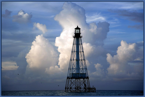 Alligator Light...................Islamorada, Florida<br /> The rising sun and storm clouds to the east combine to cast both shadow and  warm light on a line of clouds moving along the horizon.