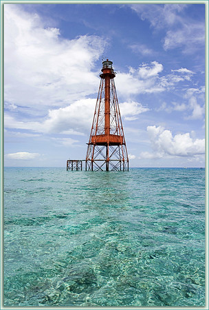 Sombrero Light is located in the Atlantic off of Marathon in the Florida Keys. Here its red structure punctuates a brilliant blue summer sky above the sparkling shallows of  Sombrero Shoal.
