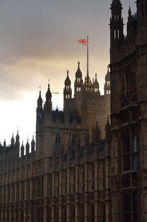 Detail of Parliament with the sun backlighting the Union Jack and a plane on final to Heathrow.