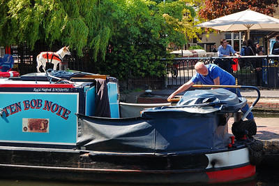 A long boat goes through the Camden Locks.