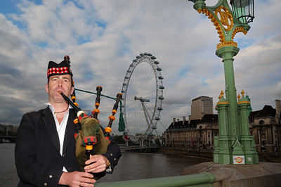 A lone piper plies his trade on Westminster Bridge.