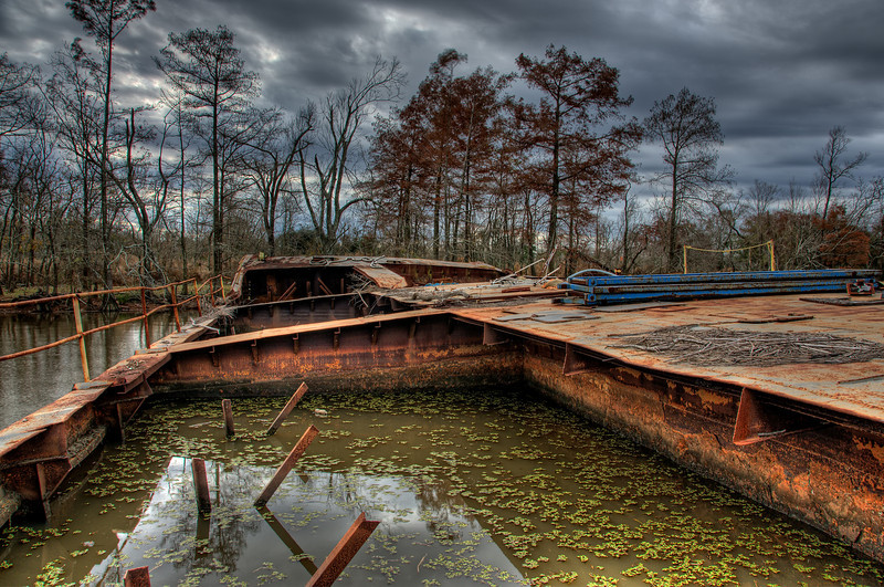 On the deck of a rusted out, sunken barge.