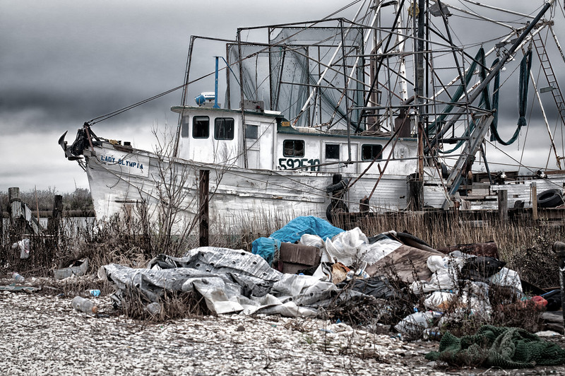Lady Olympia shrimper resting and waiting for her next run, Cameron, Louisiana.  Trash and damage courtesy of hurricane Rita.
