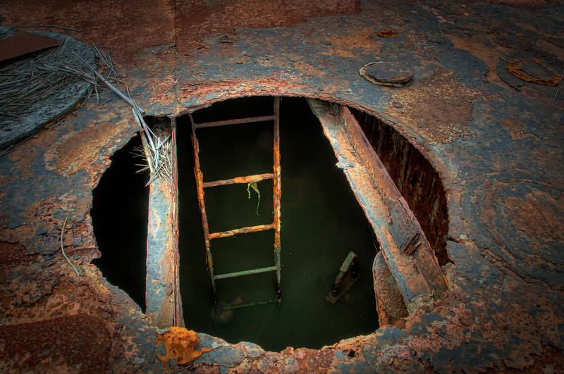 Man hole on the deck of a rusted out, sunken barge.