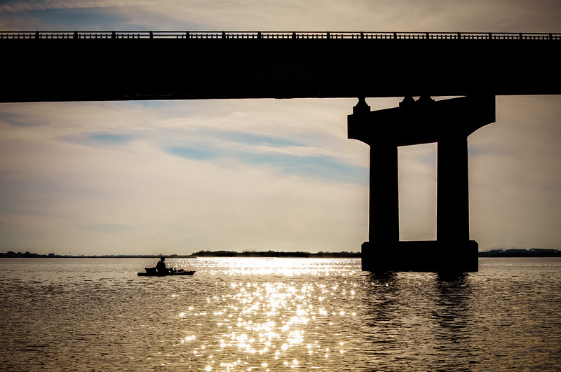 Kayak fisherman under the I210 bridge in Lake Charles, LA