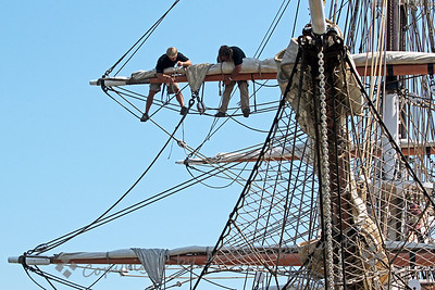 High in the Rigging ~ Two courageous and agile crewmen work, high in the rigging of the Brig Pilgrim, preparing the sails.