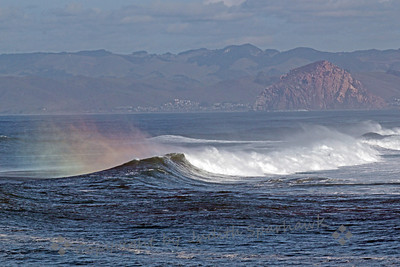 "Rainbow at the Rock ~ Looking across the bay at Morro Rock, known locally as ""The Rock"", the mist blowing off the wave tops formed rainbows in the early morning sun.  I understand that these are really called ""sunbows"", since they weren't caused by rain.  No matter, it was a beautiful sight."