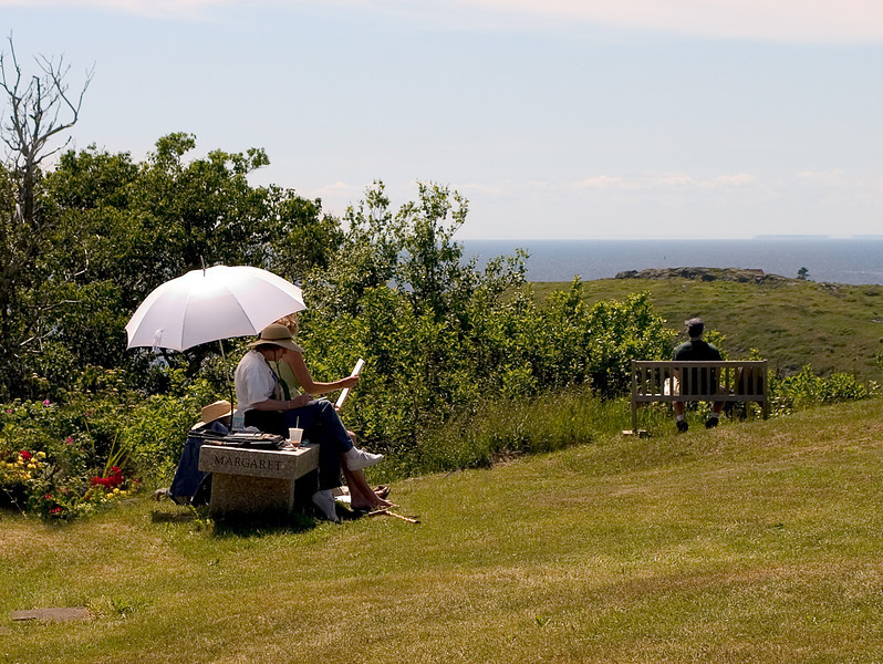 People sketching under a sun umbrella in Maine with the ocean in the distance
