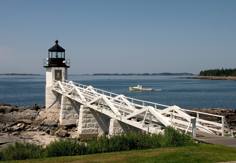 Light House in Maine with a small fishing boat in the distance