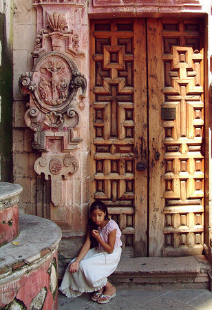 Taxco, Mexico.  A young girl waiting outside the baroque Santa Prisca Cathedral during mass.