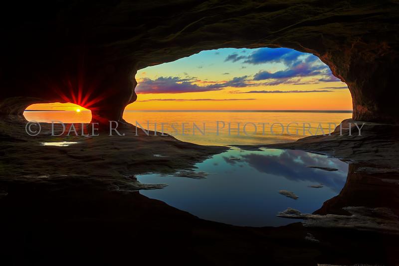Lake Superior sunset from a water worn sand stone cave near Munising, Michigan.
