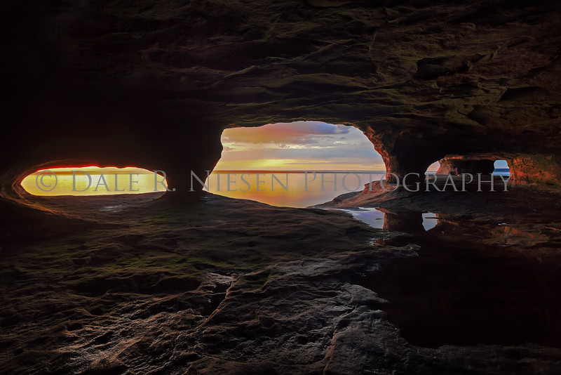 Sunset over Lake Superior from a water worn sand stone cave near Munising, Michigan.